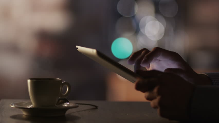 Man Using Tablet PC and Drinking Coffee in Cafe. Close-Up. Shot on RED Digital Cinema Camera in 4K (ultra-high definition (UHD)), so you can easily crop, rotate and zoom, without losing quality!