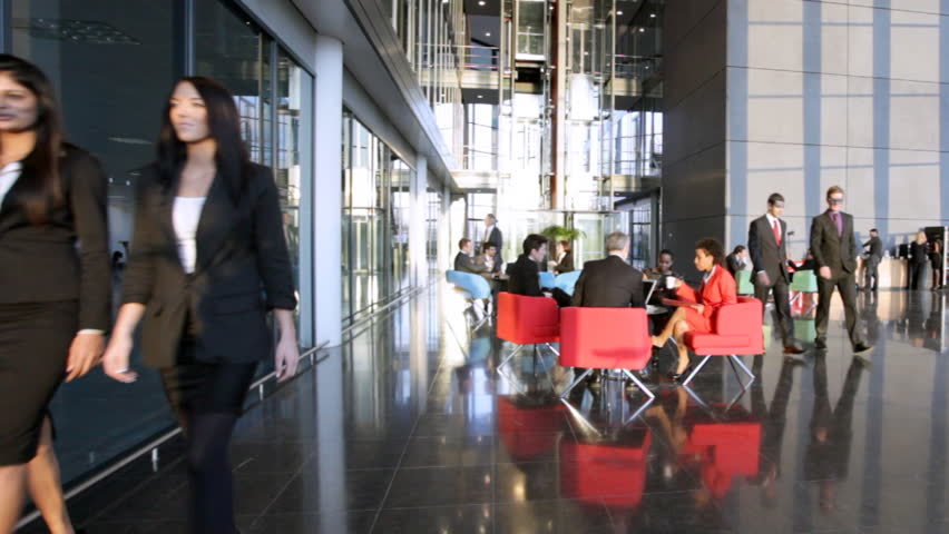 Business people inside a modern office building. Slow motion.