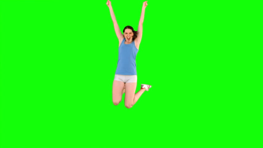 Energetic young model in sportswear jumping on green background #4527515