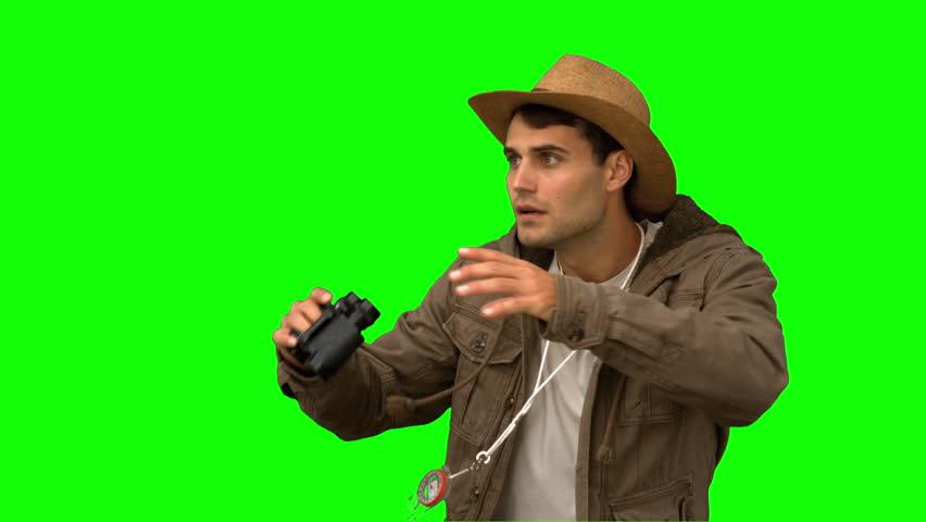 Man wearing a coat using binoculars on green screen in slow motion