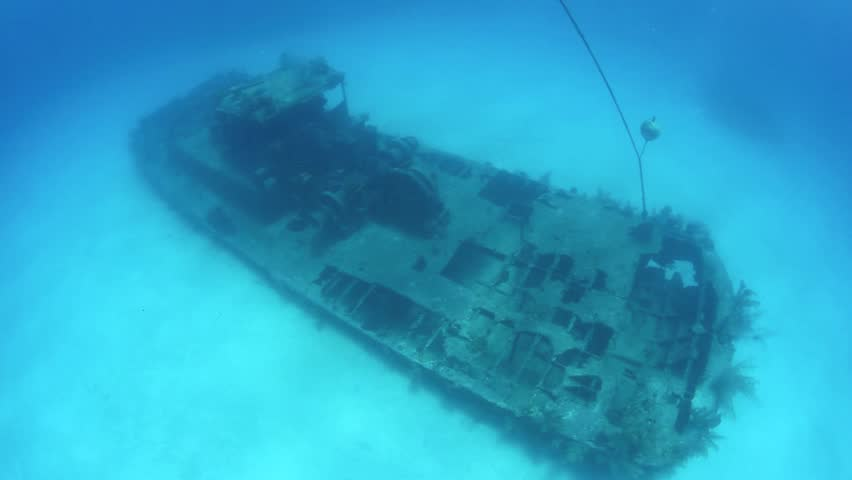 A shipwreck lies on white sand just off the island of Grand Cayman.  The deteriorating wreck acts as an artificial reef, providing habitat for fish and invertebrates.