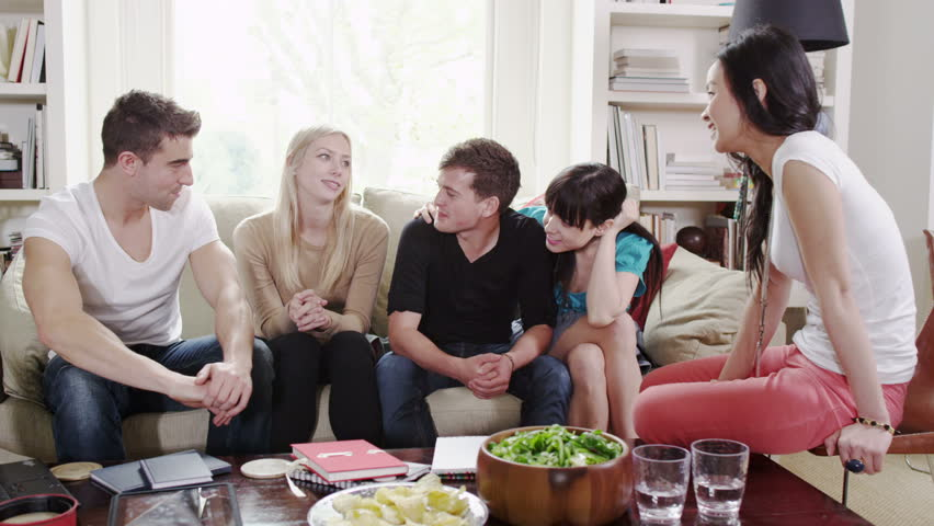 Young university friends have a social gathering in a student house.