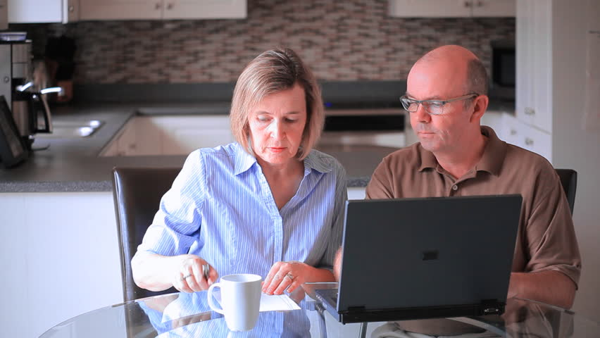 Middle Aged Mature Couple At Home In The Kitchen Using A Laptop Computer To Pay Bills And Prepare Income Tax Returns | Shutterstock HD Video #4549655