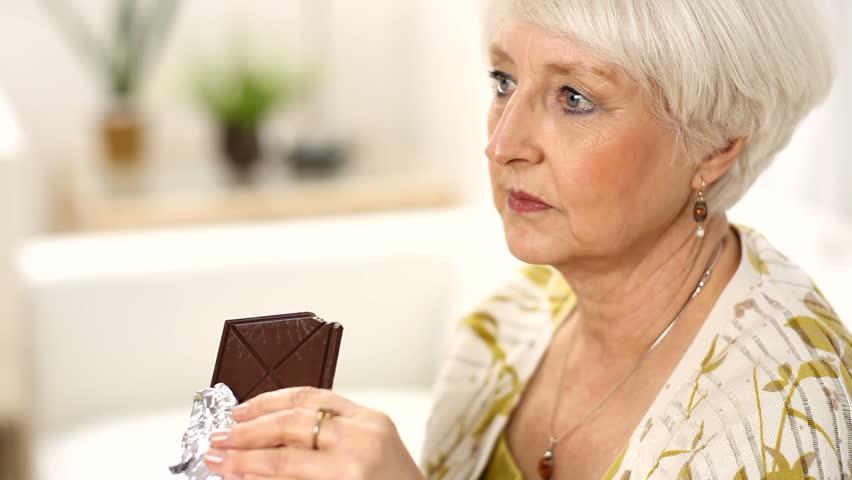 Senior woman takes bite of chocolate bar
