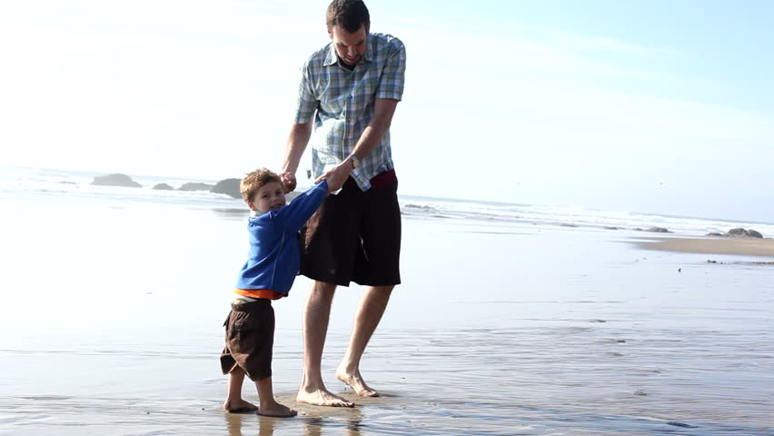 Father spinning around with son at beach