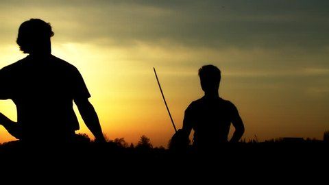 Men at sunset fighting with swords