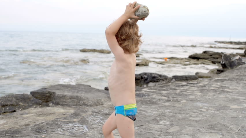 Slow Motion Shot Of A Little Red-Haired Boy Throwing A Stone Into The Sea.