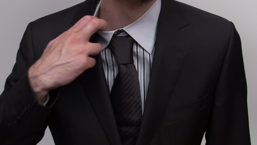 Businessman adjusts tie