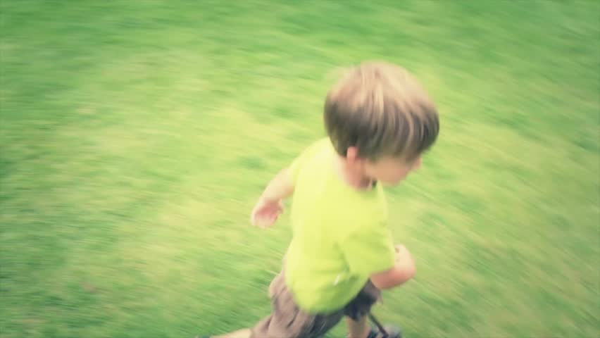 A little boy running on the grass at the park