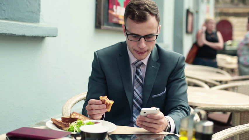 Businessman with smartphone during lunch in cafe