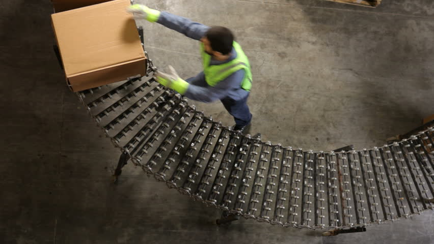 Man in shipping warehouse moves boxes along conveyor | Shutterstock HD Video #4619918