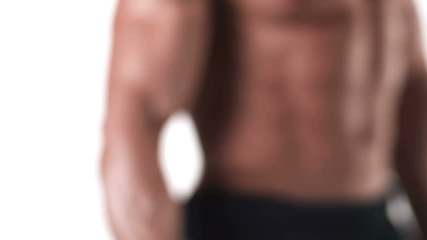 Close up shot of a muscular bodybuilder doing dumbbell curls with his large bicep muscles on a white background, with a camera pan, and rack focus