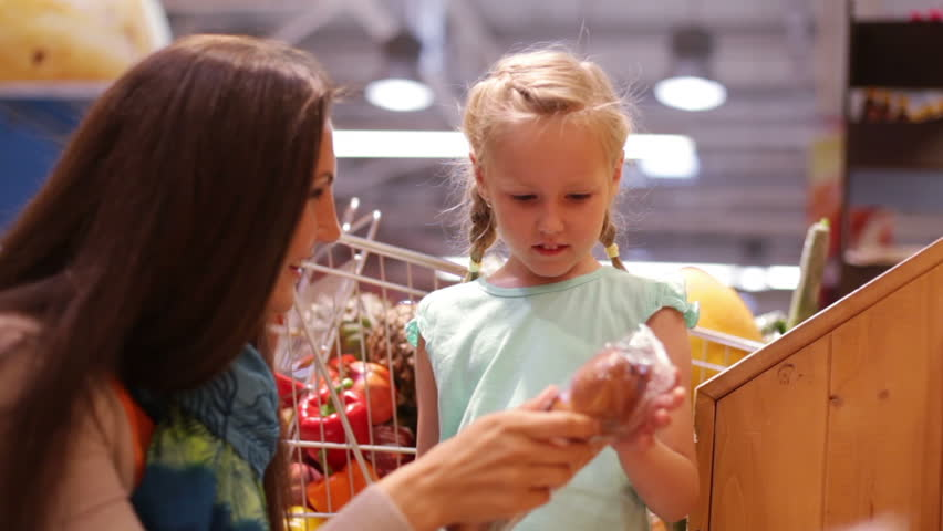 Caring mom buying sweet pastry for her little daughter | Shutterstock HD Video #4623545