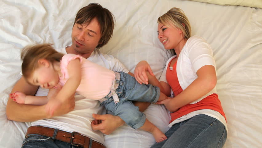 Family with young child playing together on bed