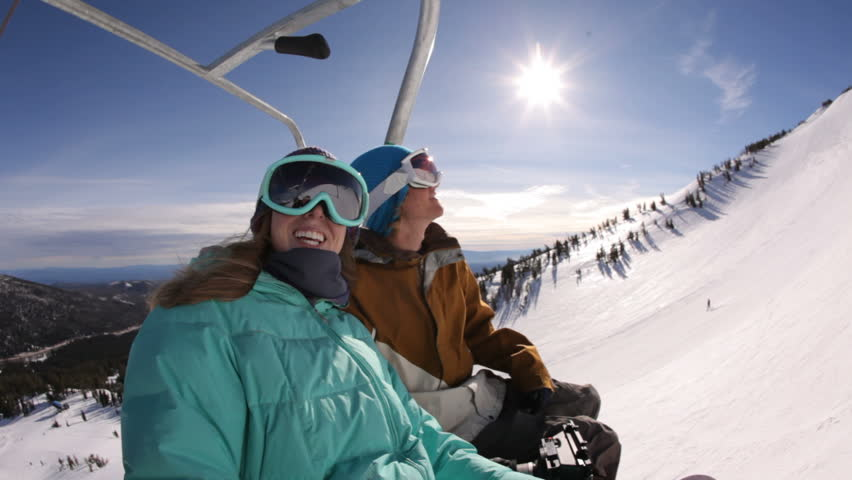 Two snowboarders riding up ski lift