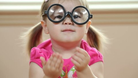 Young girl playing with silly glasses