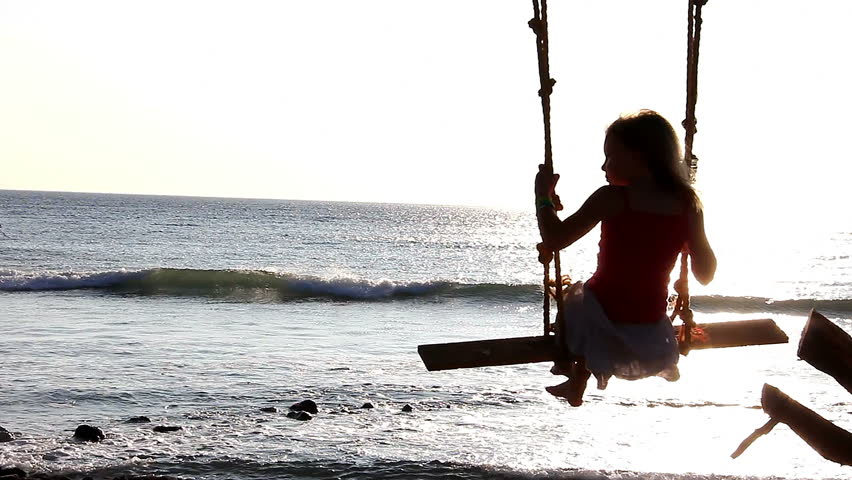A girl swings on a tree branch overlooking the sea