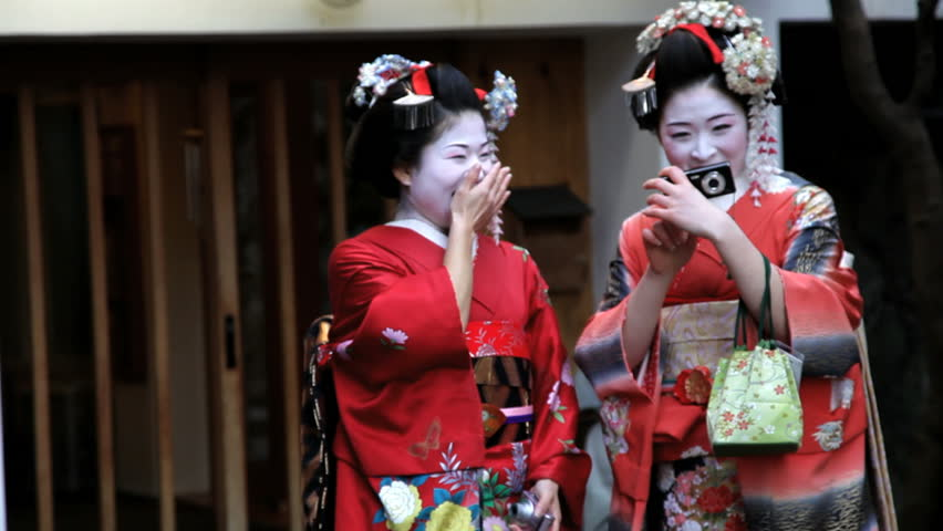 Japan - March 2011: Two Japanese Geishas posing and taking pictures of themselves in the street and laughing in Japan in March, 2011