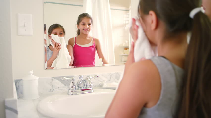Two Young Girls Look In The Mirror In The Bathroom Together As They Play  With Their