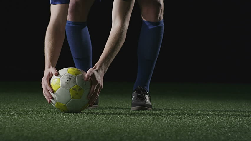 A soccer play sets the ball down and then steps back to kick it. Close up shot.