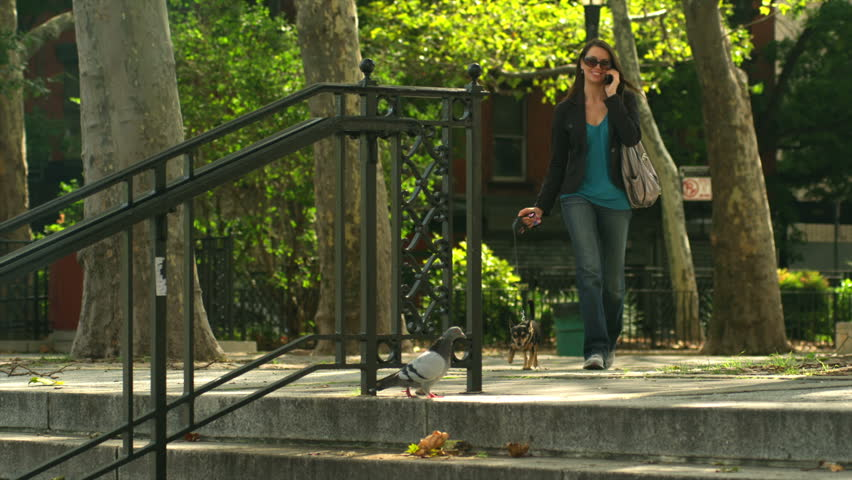 Woman talks on her cell phone as she walks with her dog. Wide shot.