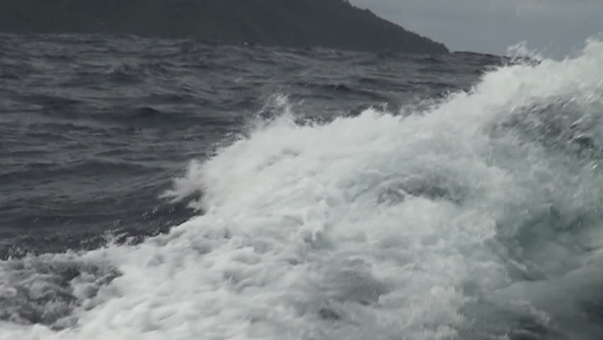 Slow motion of a rough sea with a tropical island in the background