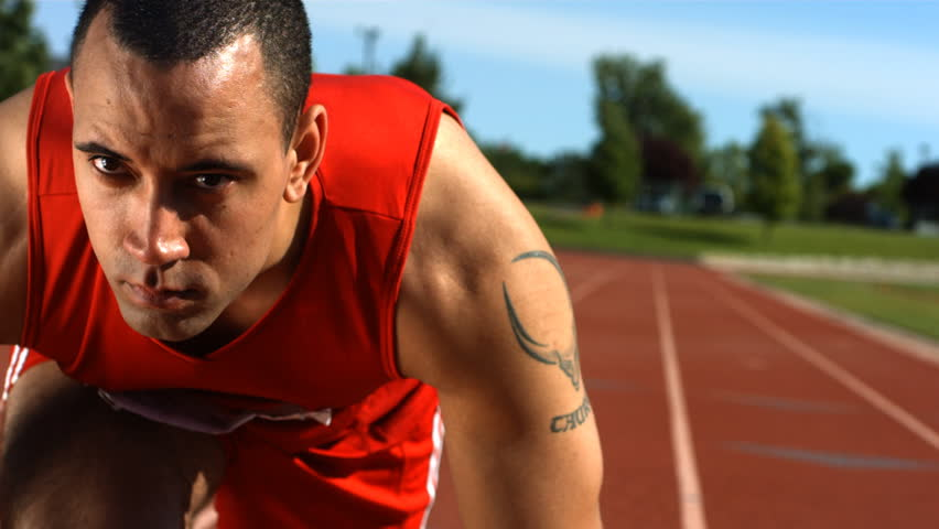 Closeup of track runner at starting line, slow motion