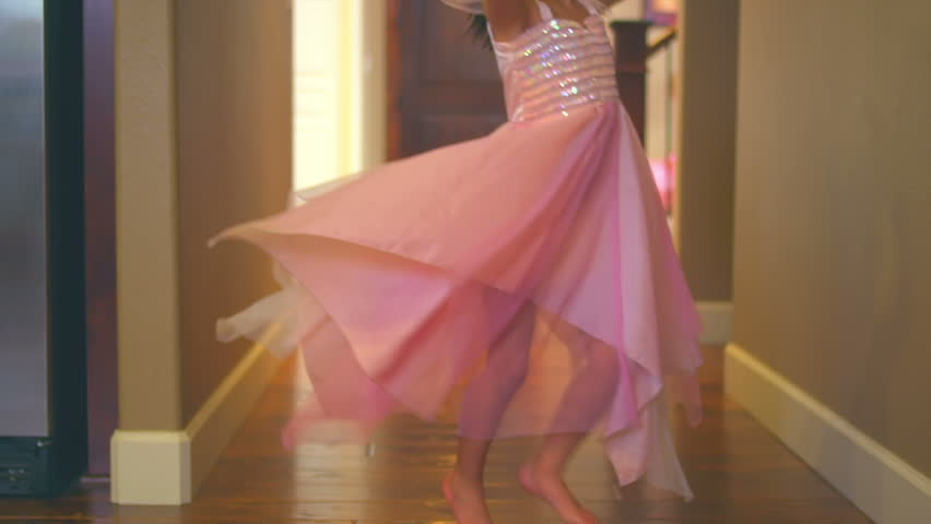 A little girl is dressed up in a ballerina costume dances through the hallway. Medium slow motion dolly shot.