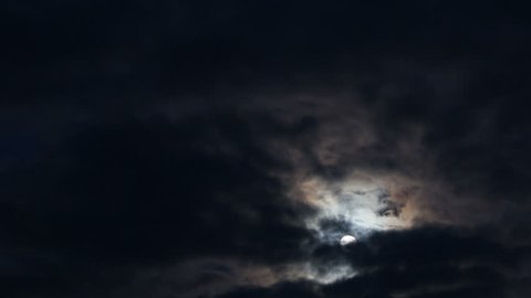 Moon rising through clouds. Time lapse.