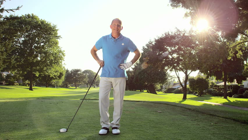 Portrait of golfer smiling into the camera. Wide shot.