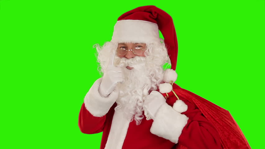 Santa Claus carrying his bag, looks at the camera sends a kiss and wave, Green Screen
