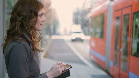 A attractive young woman waits for the tram while working on her digital tablet. Close up shot.