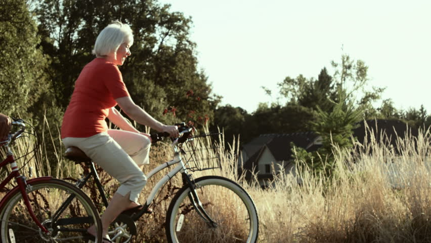 Happy couple take a bike ride together down a side walk. Wide shot. | Shutterstock HD Video #4682090