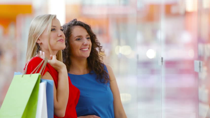 Ladies having fun standing by the shopping window in the mall | Shutterstock HD Video #4685192