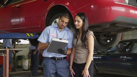 Mechanic in auto repair shop helps customer
