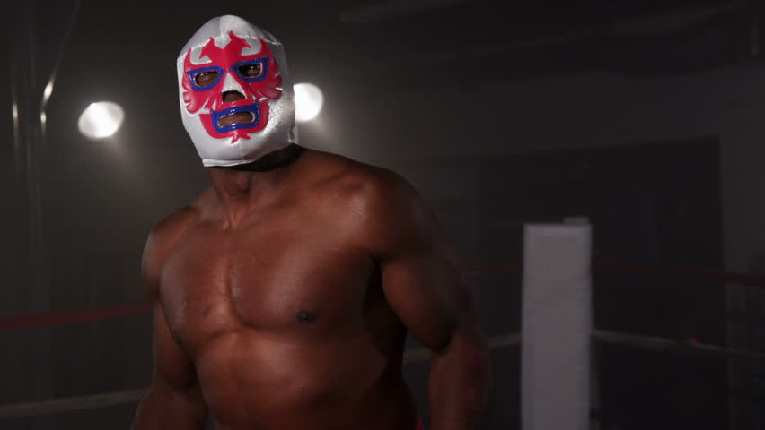 Masked wrestler flexing muscles and intimidating opponent