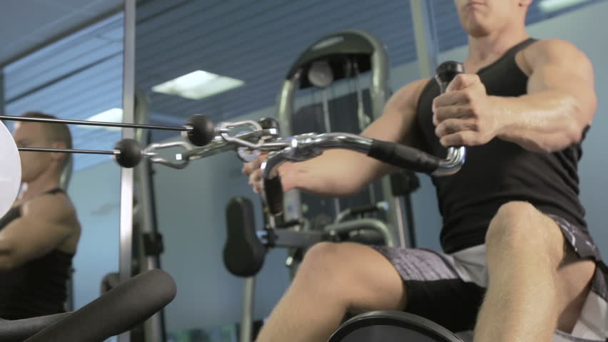 Young Muscular Man Training Hard On Rowing Machine In Fitness Studio
