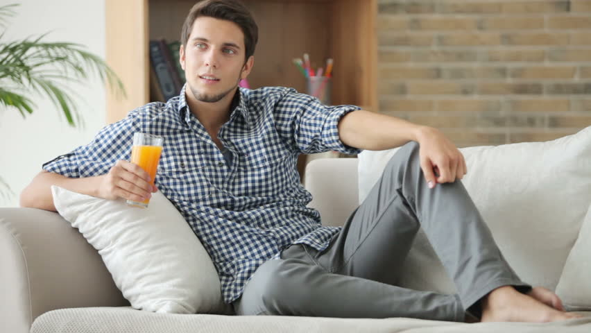 Cheerful guy relaxing on sofa holding glass of juice and smiling