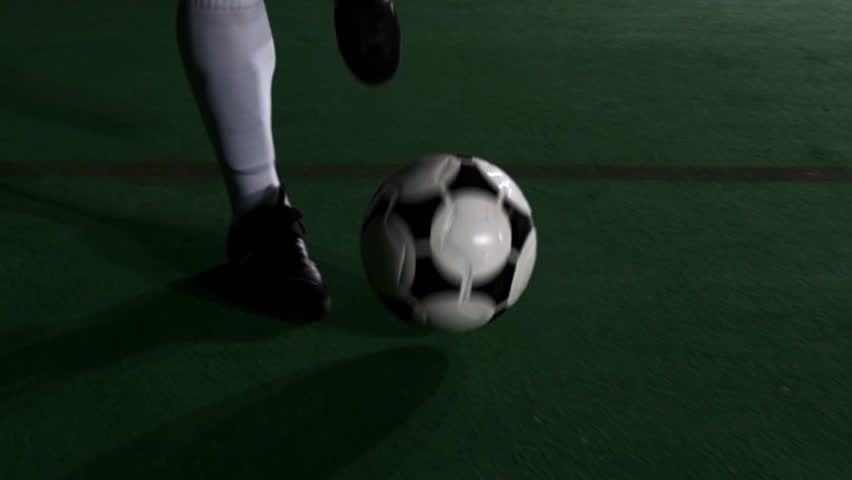 Close up of a soccer player's feet as he dribbles and does tricks with a ball