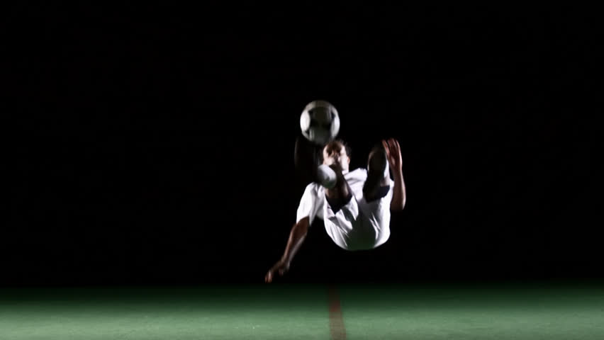 An isolated soccer player bounces a ball off his chest and then bicycle kicks it