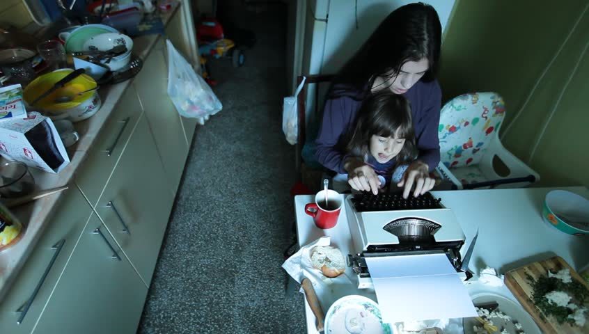 Mother with obsolete vintage typewriter typing in the kitchen and taking care of little baby girl child. Daylight urban indoor scene. Business, motherhood and childhood concept and idea..  | Shutterstock HD Video #4730795