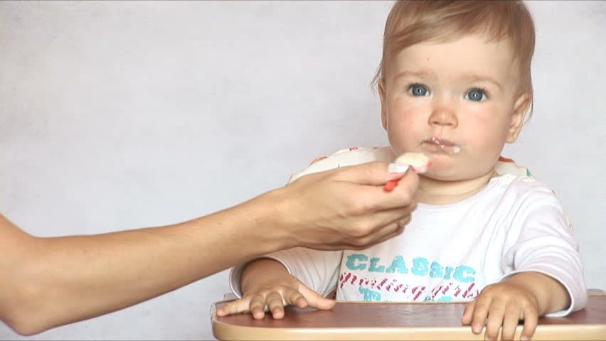 Baby sits at a children's little table. Mum feeds the child with porridge.