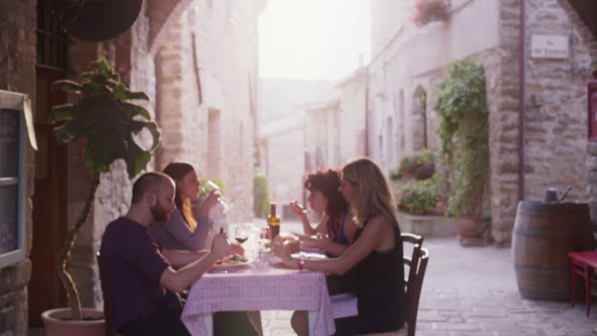 Four friends eating gourmet dishes in a elegant restaurant