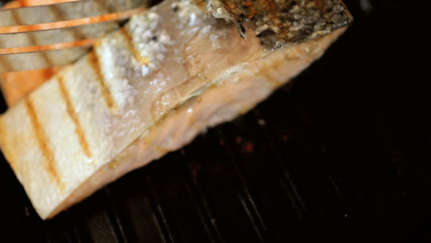 Delicious Alaskan salmon steaks with grill marks and crispy skin being cooked on a hot grill