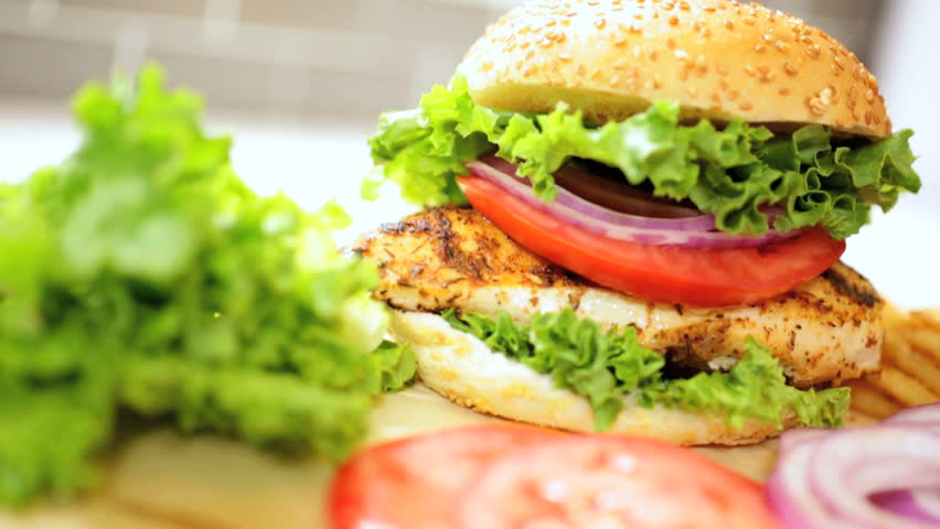 Juicy chicken breast sandwich on a sesame seed bun with fresh lettuce, tomato, and onions #4745054