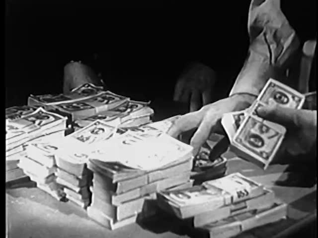 Medium shot of man stacking bundles of money on table