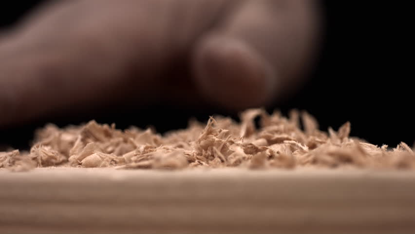 Hand brusing off wood shavings, slow motion