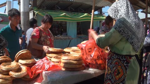 OSH, KYRGYZSTAN - 30 JUNE 2013: People are selling and buying bread at the Osh bazaar in Kyrgyzstan