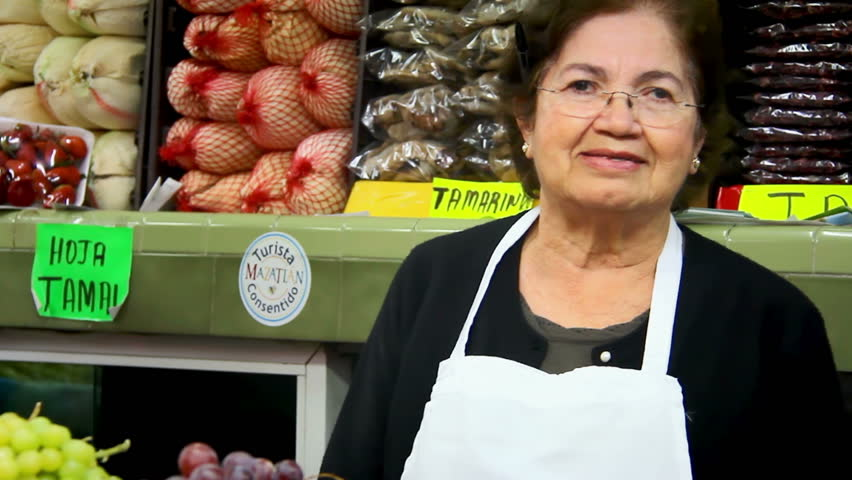An older Mexican woman poses for the camera in a market standing in front of the vegetables