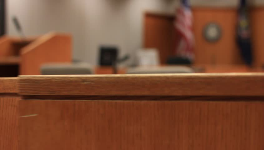 A wooden half door swings in a courtroom.